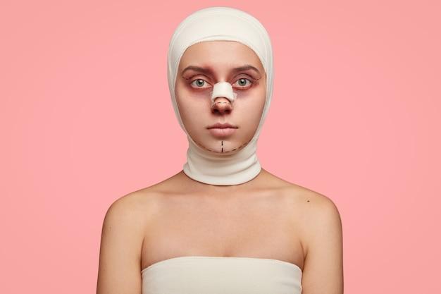 Colpo isolato di ragazza ha spalle nude, viso segnato in linee, avvolto con benda, preparato per il trattamento del viso Foto Gratuite