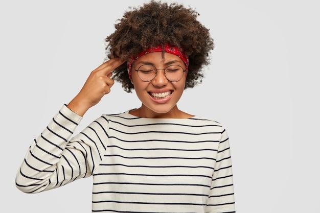 Colpo isolato di felice giovane donna dalla pelle scura si diverte al coperto Foto Gratuite