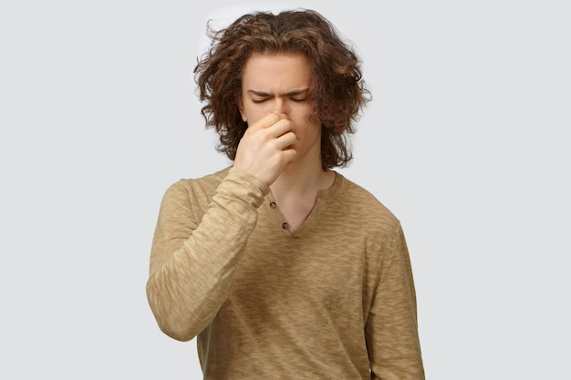 Isolated shot of handsome frustrated young european male in long sleeved top closing eyes and pinching nose, feeling disgusted because of bad smell or stink of sweaty armpits or dirty socks Free Photo