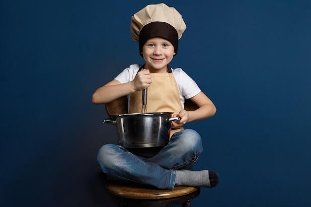 Colpo isolato di bambino maschio allegro felice in jeans, copricapo da chef e grembiule, seduto a gambe incrociate sulla sedia di legno, tenendo la casseruola, sbattendo le uova con lo zucchero mentre si prepara la pasta per la torta Foto Gratuite