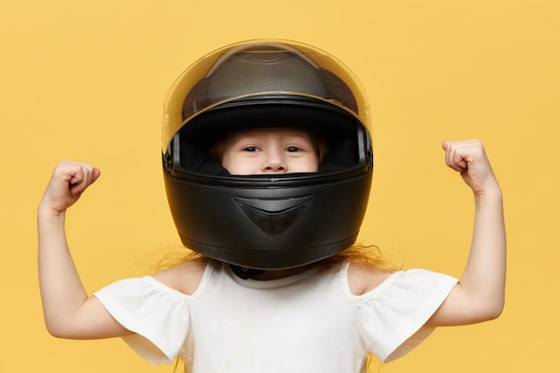 Isolated shot of little girl racer posing against yellow wall wearing black safety motorcycle helmet demonstrating her bicep muscles. people, extreme sports and adrenaline concept Free Photo