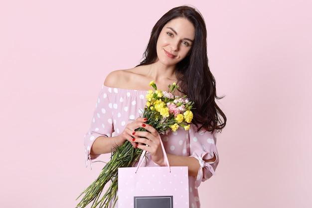 魅力的な若いヨーロッパの女性の分離ショットは黒い長い髪をして、水玉のドレスを着て、ギフトバッグと花を保持し、淡いピンクの壁でポーズし、国際女性の日を祝います 無料写真
