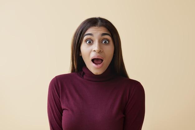 느슨한 스트레이트 머리가 입을 넓게 열고 말을 잃어버린 아름다운 아프리카 계 미국인 여성의 고립 된 샷, 놀란 표정, 큰 판매 가격 또는 놀라운 정보로 충격 무료 사진