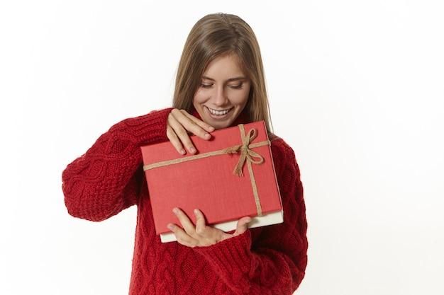 슬픈 실망한 표정을 가진 생일 선물 열기 상자를 들고 세련된 안경과 적갈색 풀오버에 아름다운 젊은 아가씨의 고립 된 샷은 안에 무엇이 마음에 들지 않습니다 무료 사진