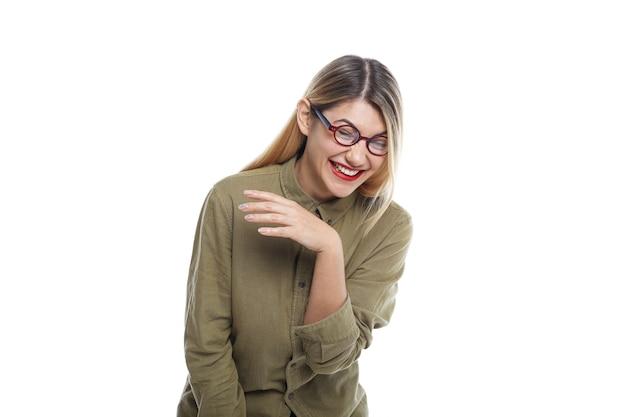 Изолированный снимок веселой эмоциональной красивой девушки-хиптера, громко смеющейся над забавной шуткой во время просмотра комедии дома, закрывая глаза, наклоняясь вперед и дрожа от истерического смеха Бесплатные Фотографии