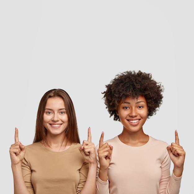 두 검지 손가락이 위쪽으로 다른 레이스 포인트의 쾌활한 여성의 고립 된 샷 무료 사진