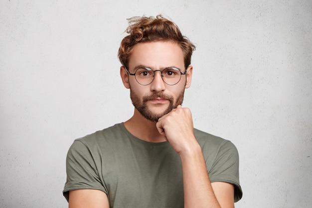 自信を持ってのひげを生やした男の孤立したショットはカメラに直接見える、真剣な表情 無料写真