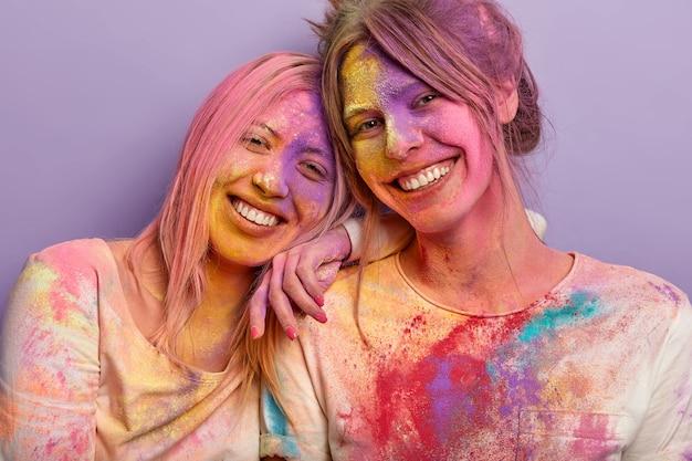 お互いの顔に色の粉を塗った後に疲れたフレンドリーな楽観的な女の子の孤立したショットは、近くに立って、ホーリーの休暇中に来る春を祝います。明るい色の2人の女性のショット 無料写真
