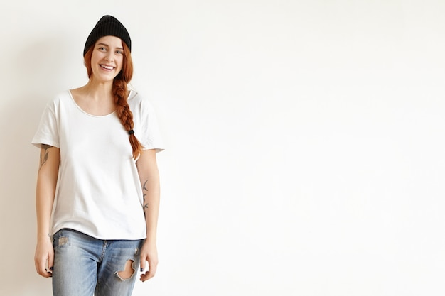 白い壁でポーズ、三つ編みで生姜髪を着て幸せな女の子の分離ショット 無料写真
