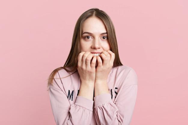 Изолированная съемка довольно женской модели кусает ногти, так как чувствует себя очень нервной и смущенной Бесплатные Фотографии