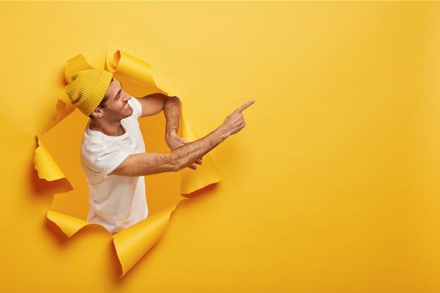 Изолированный снимок довольной мужской модели, стоящей боком в отверстии для бумаги, одетой в желтый головной убор Бесплатные Фотографии