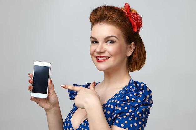 レトロな服と赤い口紅を身に着けて幸せに笑って、現代の電子機器を促進し、一般的な携帯電話を保持しているスタイリッシュな若い女性モデルの孤立したショット 無料写真