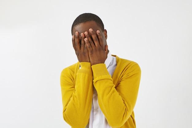 黄色いカーディガンのポーズをとって、両手で顔を覆い、身を隠し、罪悪感、恥ずかしがり屋、恥ずかしがり屋、恥ずかしがり屋、または怖い服を着た、認識できない暗い肌の男性の孤立したショット 無料写真