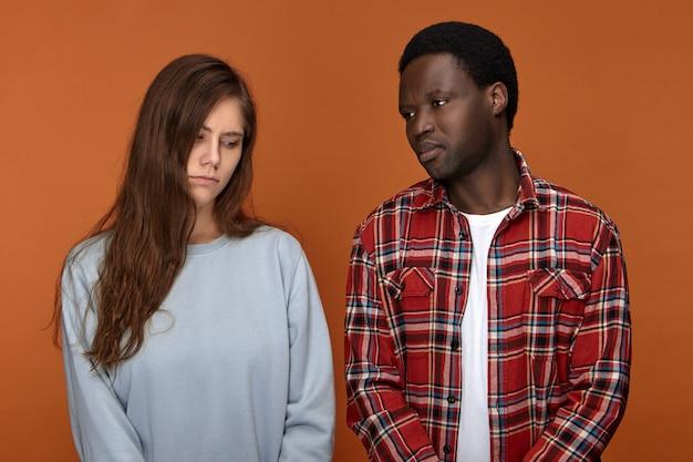 彼らが別れなければならないので不幸な表情をしている動揺している若い白人女性とアフリカ系アメリカ人男性の孤立したショット。問題に直面し、悲しい異人種間の落ち込んでいるカップル 無料写真