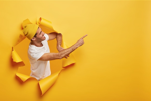 Isolated shot of satisfied male model stands sideways in paper hole, dressed in yellow headgear Free Photo