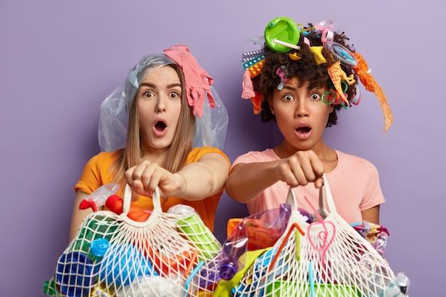 Colpo isolato di donne multietniche sbalordite fissano con occhi infastiditi e sorpresi, tengono sacchetti di rete pieni di rifiuti di plastica, andando a riciclare i rifiuti riutilizzabili, stare vicino al muro viola Foto Gratuite