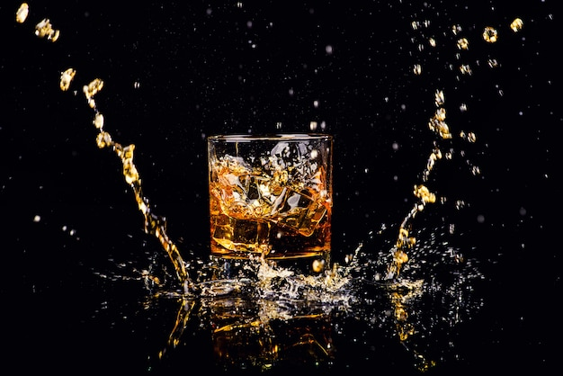 Isolated shot of whiskey with splash Premium Photo