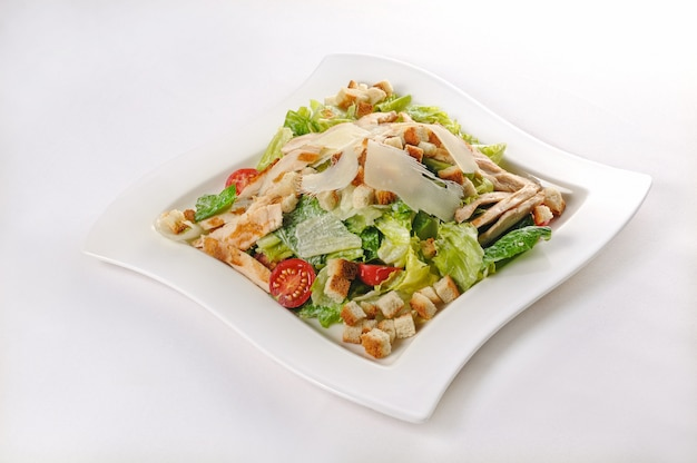 Isolated shot of a white plate with ceasar salad - perfect for a food blog or menu usage Free Photo