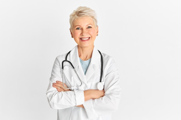 Colpo isolato di felice successo maturo medico anziano che indossa un unifrom medico e uno stetoscopio con un'espressione facciale allegra, sorridendo ampiamente, tenendo le braccia incrociate sul petto Foto Gratuite