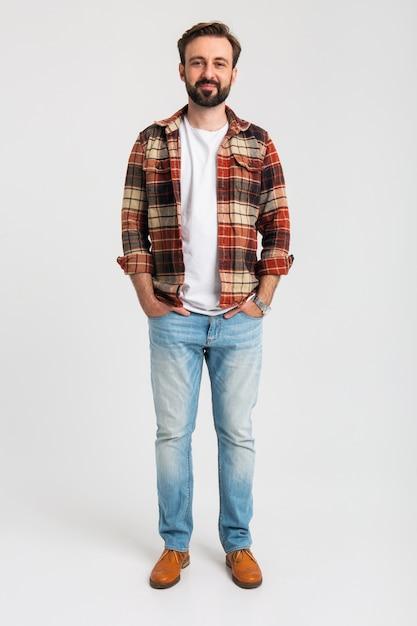 Изолированные улыбается красивый бородатый мужчина в хипстерской одежде, одетый в джинсы Бесплатные Фотографии