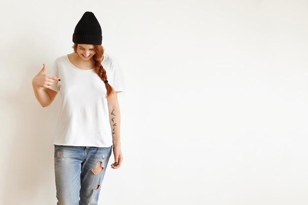 彼女は空白の白いtシャツを指して彼女を見下ろす三つ編みを持つ若い女性の分離スタジオショット 無料写真