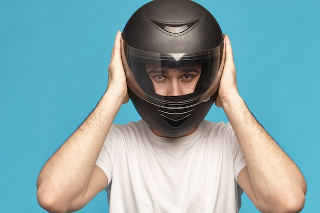 Isolated studio shot of self determined serious young caucasian male biker taking on stylish black motorcycle helmet Free Photo