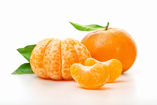 Isolated tangerines. half of peeled tangerine and whole mandarin or orange fruit with green leaves isolated on white background. close up. Premium Photo