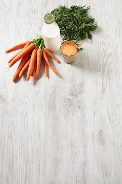 Isolato vista dall'alto sul tavolo di legno, fattoria raccolto di carote che giace vicino a una bottiglia e un bicchiere riempito con mix di succo fresco naturale e latte con cannuccia dorata in esso Foto Gratuite