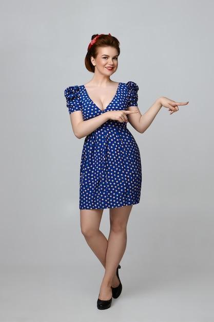 Изолированные вертикальный полный портрет веселой красивой молодой кавказской прикалывать девушку в винтажном платье, радостно улыбаясь, рекламируя какой-то продукт, указывая указательными пальцами Бесплатные Фотографии