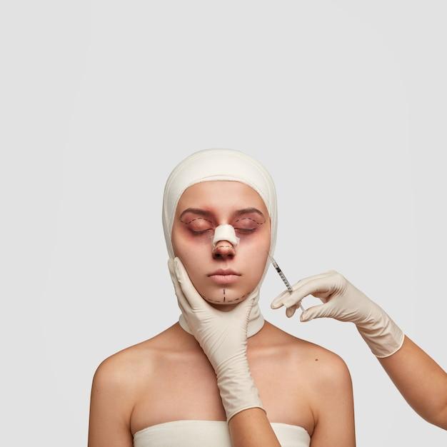 Colpo verticale isolato femmina con lividi e segni di sollevamento, ottiene l'iniezione in faccia prima dell'operazione di plastica Foto Gratuite