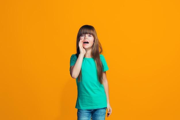 Isolato su giallo giovane ragazza adolescente casuale che grida allo studio Foto Gratuite
