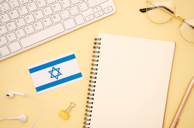Israel flag next to empty notebook Free Photo