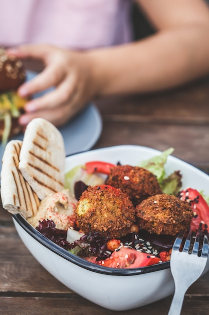 Israeli street food. falafel salad with hummus, beetroot and vegetables in bowl in a restaurant. Premium Photo