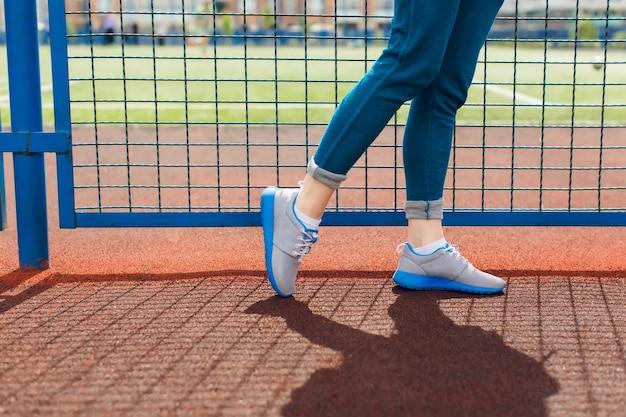 スタジアムの青いフェンスの近くを歩く少女の足の写真です。彼女はブルーのラインとブルーのパンツが入ったグレーのスニーカーを着ています。 無料写真