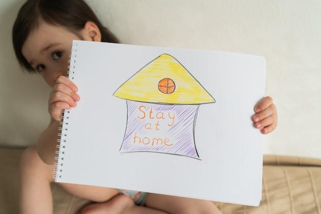 パンデミックの間、家にいることが重要です。コロノウイルス世界検疫。図面を手に持った少女 Premium写真