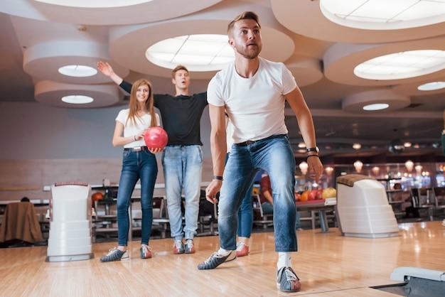 Deve essere uno sciopero. i giovani amici allegri si divertono al bowling durante i fine settimana Foto Gratuite