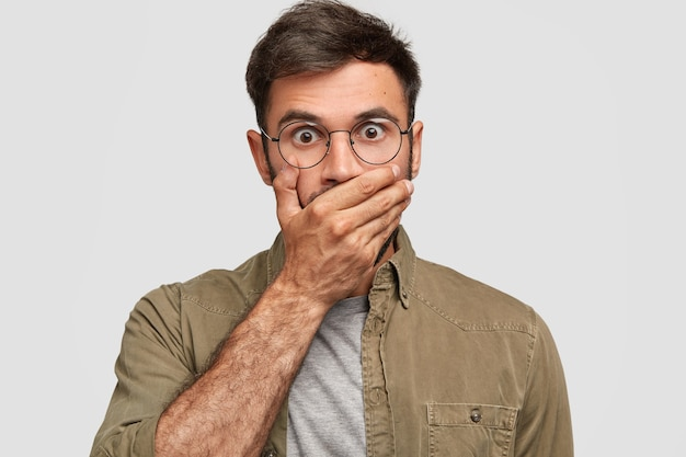 It`s awful! stunned bugged eyed male with surprised expression, covers mouth with palm, keeps importnat information in secret, has dark hair, dressed in casual shirt, poses indoor. people and reaction Free Photo
