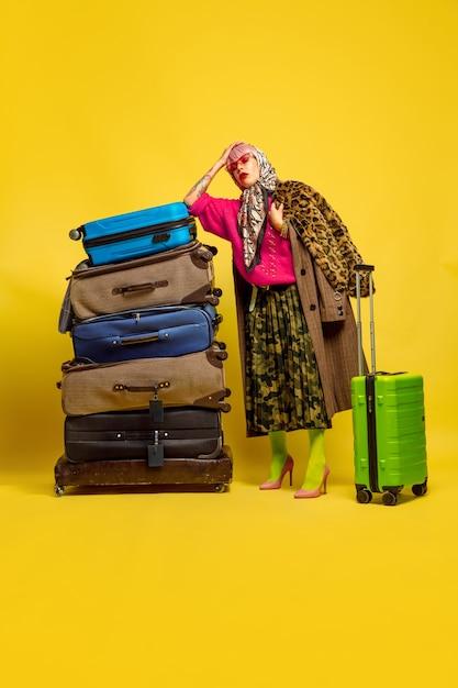 Трудно быть влиятельным лицом. много одежды для путешествий. портрет кавказской женщины на желтом фоне. красивая блондинка модель. концепция человеческих эмоций, выражения лица, продаж, рекламы. Бесплатные Фотографии