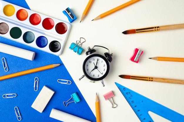 学校に戻る時間です。文房具と目覚まし時計のトップビュー Premium写真
