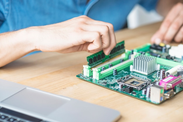 It technician repairing hardware equipment's on wooden table Free Photo
