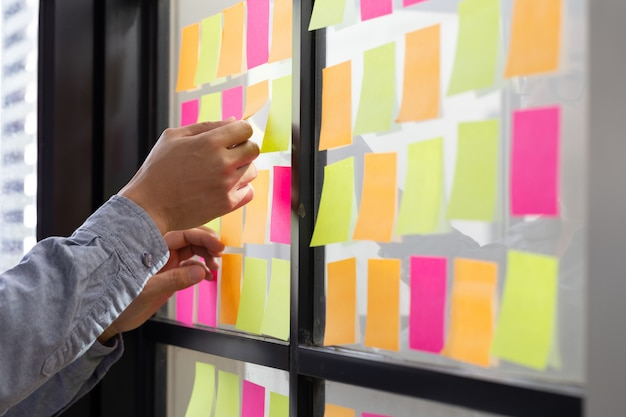 It worker tracking his tasks on kanban board. using task control of agile development methodology. man attaching sticky note to scrum task board in the office Premium Photo