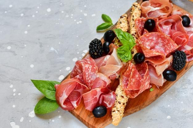 Italian antipasti prosciutto, salami, bresaola olives tomatoes and grissini bread sticks. aperitif happy hour Premium Photo