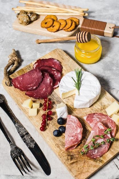 Italian antipasto with prosciutto, salami, parmesan, brie and gorgonzola cheese, honey. Premium Photo