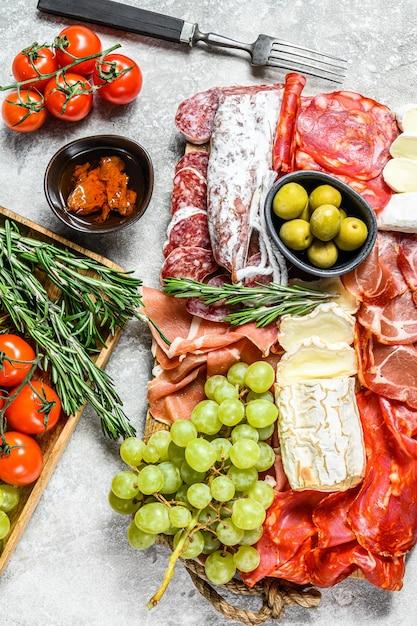 Итальянский антипасто, деревянная разделочная доска с ветчиной, ветчиной, пармой, козьим сыром и камамбером, оливками, виноградом. антипаста. вид сверху Premium Фотографии