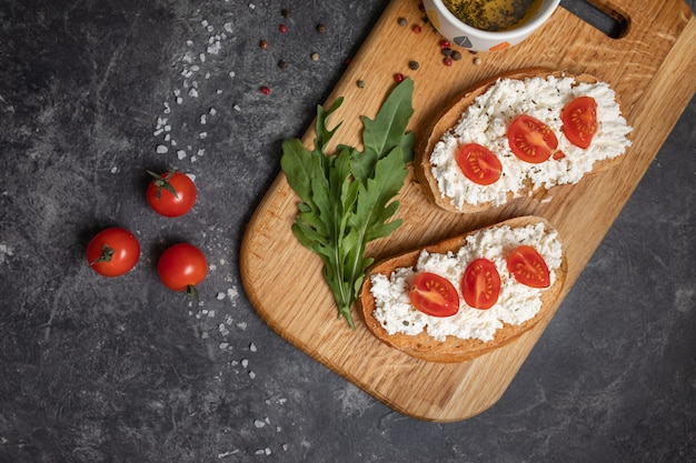 Italian bruschetta with roasted tomatoes, mozzarella cheese and herbs on a cutting board. Premium Photo