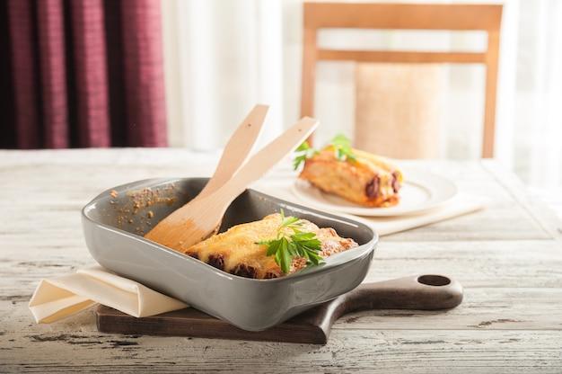 Итальянская паста каннеллони на светлом столе. плоско заложить пасту канелони крупным планом на ужин и скопировать пространство. Premium Фотографии