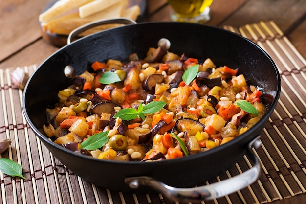 Italian caponata with frying pan on a wooden table Free Photo