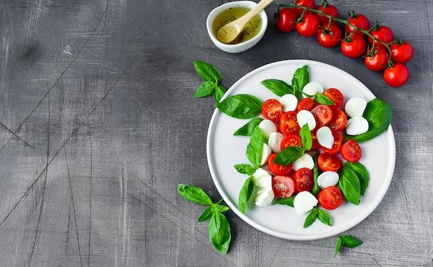 Italian caprese salad: red tomatoes, mozzarella and basil, italian cuisine. healthy lunch. Premium Photo