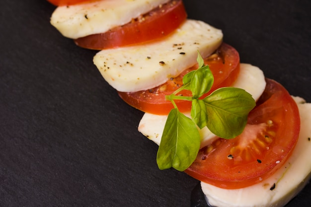 Italian caprese salad with alternating slices of tomato and mozzarella cheese seasoned with pepper and fresh basil leaves Free Photo
