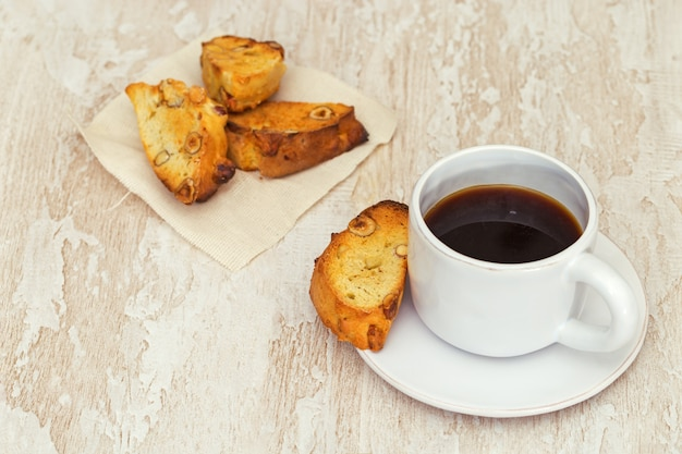 Italian dry biscuits biscotti with cup of coffee or black tea on wood table. Premium Photo